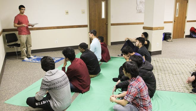 Mohammed Ismail leads a prayer service with the University of Iowa Muslim Student Association in the Lucas Dodge Room at the Iowa Memorial Union Friday, Nov. 20, 2015.