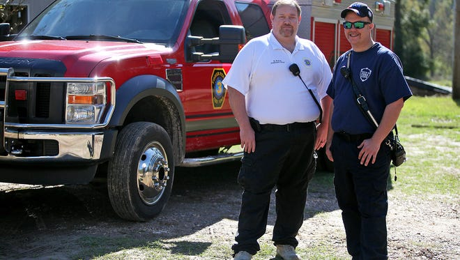 Bobby Rufus, chief of the Fisher Ferry Volunteer Fire Department, left, and his stepson Joshua Davies, serving as assistant chief, pose for a photo in Vicksburg, Miss.