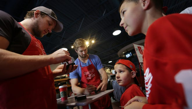 Caleb Godawa, 10, from right, and his brother Brendan Godawa, 7, of Saint Clair Shores look on as Detroit Red Wings players Darren Helm and Justin Abdelkader sign memorabilia during the 10th annual Red Wings Bell Ringing Competition for The Salvation Army at Hockeytown Authentics in Troy on Friday, Dec. 4, 2015.