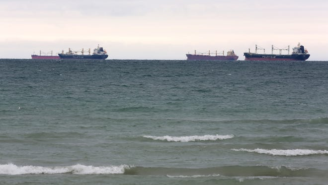 A Great Lakes freighter on Lake Huron heads past sailboats in July of 2014.