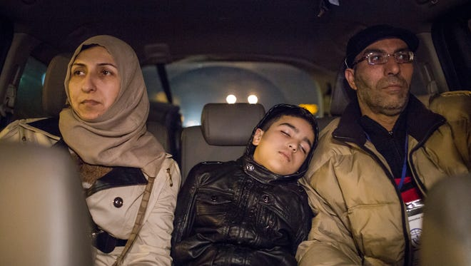 Arab Buteh, 8, falls asleep sitting between his parents Nayef Buteh, right, 45, and Feryal Jabur, 41, Syrian refugees, on their way to a hotel after arriving at Detroit Metro Airport last month.  Salwan Georges:  We stood in baggage claim at Metro Airport's McNamara Terminal when I greeted this family in their Syrian dialect. They thanked God for finally making it to the U.S. Seeing their expressions of exhaustion and relief took me back to the moment when I first set foot in the U.S. It was a long journey for me and my family as well — a 14-hour flight and a five-hour wait in Chicago before we could board the plane to Detroit. For us, there was sheer happiness — we made it to the U.S.  But after that you feel lost. You're starting all over again.