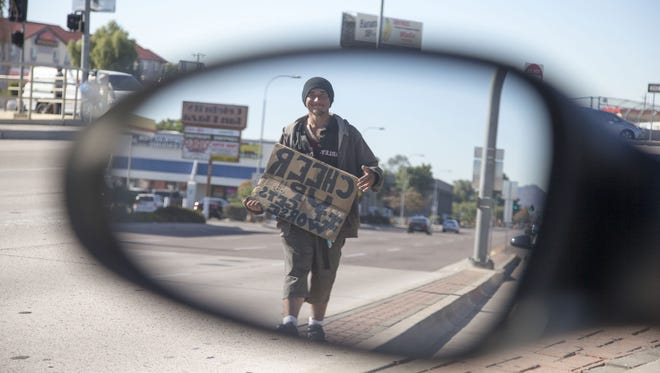 A homeless man begs on a Phoenix street. Phoenix police and city social workers try to find homeless people to provide services if they are qualify.