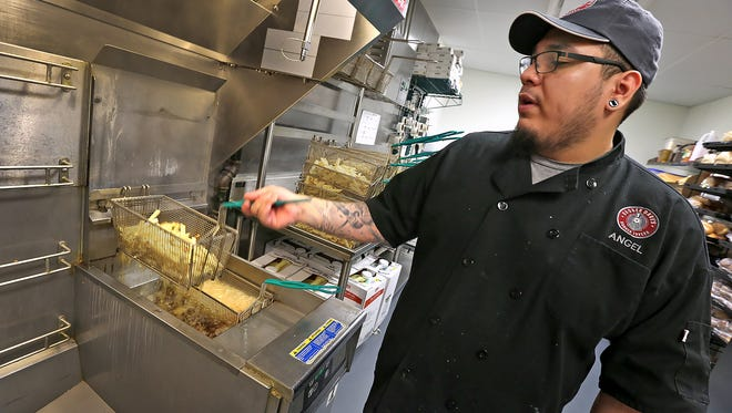 Angel Rodriguez takes fries out of the deep fry after they are blanched and before the final fry at a Bagger Dave's Burger Tavern in July 2015.