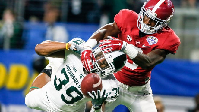 Alabama WR Calvin Ridley fights for the ball against Michigan State CB Jermaine Edmondson, during the first half of the Cotton Bowl Classic in Arlington, Texas, on Thursday.