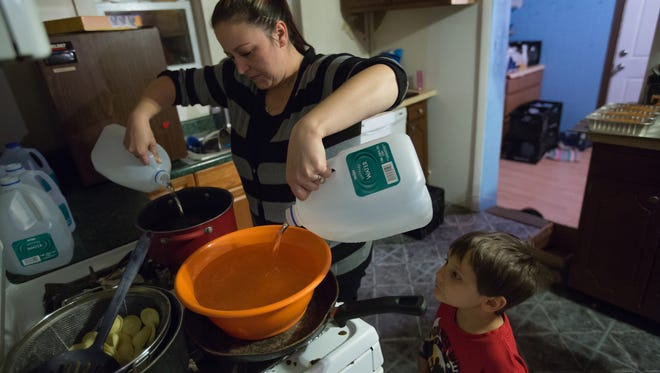 """Lee Anne Walters of Flint heated up bottled water in November for her twin sons to take a weekly bath as son, Gavin Walters, 4, looked on. """"My family will never drink from a tap again,"""" Walters told the Detroit Free Press. Flint rejoined the Detroit Water and Sewerage Department in October."""