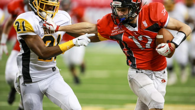 Lowell WR Gabe Steed stiff arms and grabs Detroit Martin Luther King DB Lavert Hill's face mask, during the first quarter of the Michigan High School Athletic Association football finals at Ford Field in Detroit on Friday, Nov. 27, 2015. Lowell is up 24-13 in the first half.
