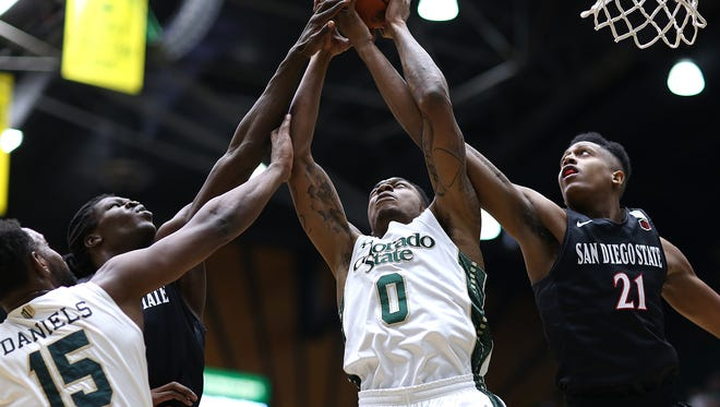 CSU's Tiel Daniels (15) and Kimana Jackson battle Malike Pope (21) and another San Diego State player for a rebound during Wednesday night's game at Moby Arena.