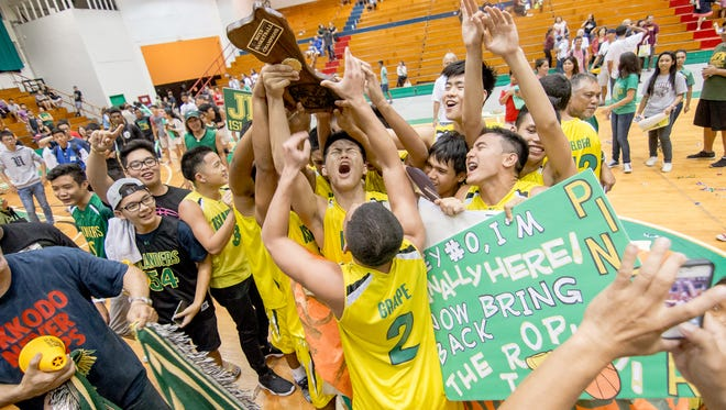 John F. Kennedy High School celebrates after beating Father Duenas Memorial School at the 2015 Independent Interscholastic Athletic Association of Guam Boys' Basketball League championship game.