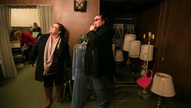 Chere Nulph (right) and Tonya McCord (left) look a light fixture in one of the rooms of the Barrick Funeral Home on Saturday, Jan. 16, 2016. The Washington residents drove to Salem just for the funeral home's closing sale after seeing it posted on Craigslist.