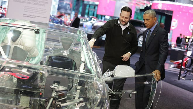 President Obama gets an explanation at the ZF display on how autonomous driving technology works at the 2016 North American International Auto Show at Cobo Center.