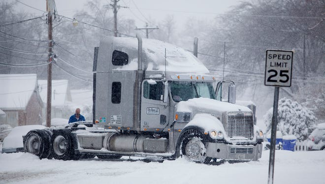 A semi-truck gets stuck on Woodford Avenue on Friday, Jan. 22, 2016, in Bowling Green, Ky. A massive blizzard began dumping snow on the southern and eastern United States on Friday, with mass flight cancelations, five states declaring states of emergency and more than two feet (60 centimeters) predicted for Washington alone. Blizzard warnings or watches were in effect along the storm's path, from Arkansas through Tennessee and Kentucky to the mid-Atlantic states and as far north as New York.
