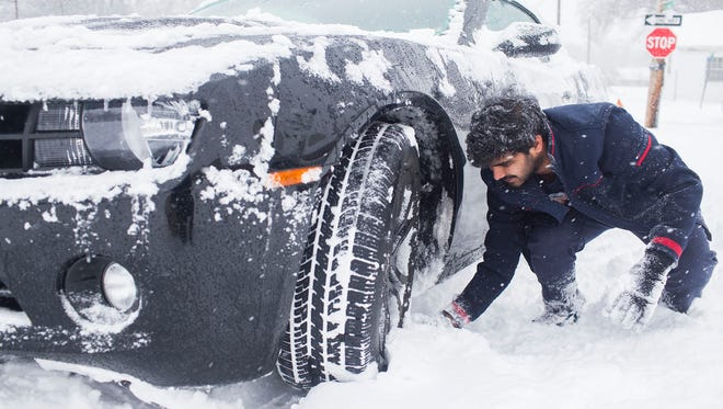Srikanth Bellamkonda of Andhra Pradesh, India, digs out his car after getting stuck in the snow on Friday, Jan. 22, 2016, in Bowling Green, Kentucky.  A massive blizzard began dumping snow on the southern and eastern United States on Friday, with mass flight cancelations, five states declaring states of emergency and more than 2 feet predicted for Washington alone. Blizzard warnings or watches were in effect along the storm's path, from Arkansas through Tennessee and Kentucky to the mid-Atlantic states and as far north as New York.