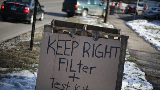 Residents pick up bottles of water and test kits at Fire Station 8 in Flint on Monday.