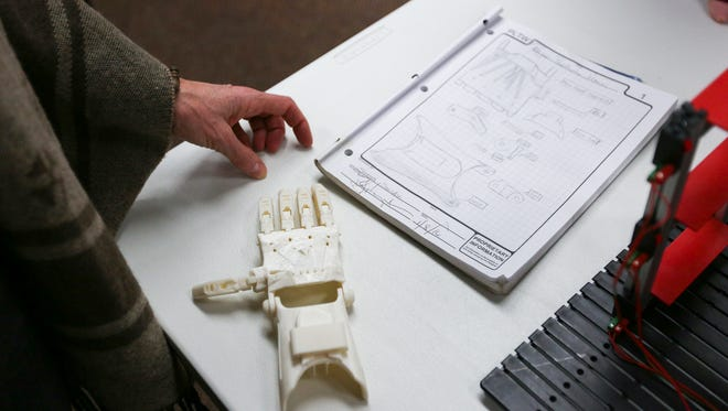 A 3D printed prosthetic hand sits next to technical drawings at Elsinore Framing in Salem on Wednesday, Feb. 3, 2016. The hand was printed by engineering students at North Salem High School, and robotics students have plans to attach sensors and motors to the model.