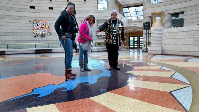 Claude Dickerson-Houilles, a Charles H. Wright Museum of African American History in Detroit volunteer, explains the symbolism in the terrazzo mural in the circular floor by Detroit artist Hubert Massey to Chicago visitors Wendy Brickhouse and Stacy Hill.