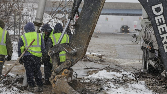 City of Flint Water Department workers fix the water main break near the Flint Water Plant on Stewart and Industrial on Tuesday .