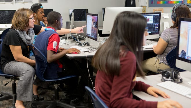 Teacher Heather Jancoski helps students in her communications class at South Mountain High School. The magnet program is funded through the $55 million Phoenix Union High School District receives each year in desegregation funding.