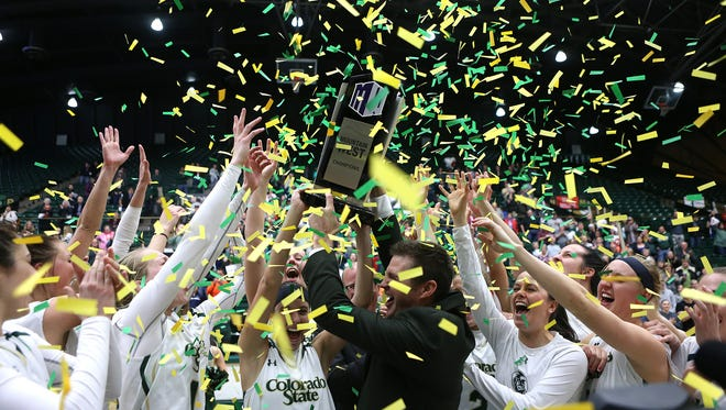 Rams coach Ryun Williams hoists the Mountain West Conference champions trophy with his team after defeating the Fresno State Bulldogs 68-55 to secure their third Mountain West Conference title in a row on Tuesday at Moby Arena.