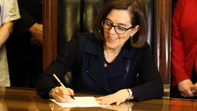 Gov. Kate Brown signs Senate Bill 1532, increasing Oregon's minimum wage on a tiered system, at the State Capitol in Salem on Wednesday, March 2, 2016.