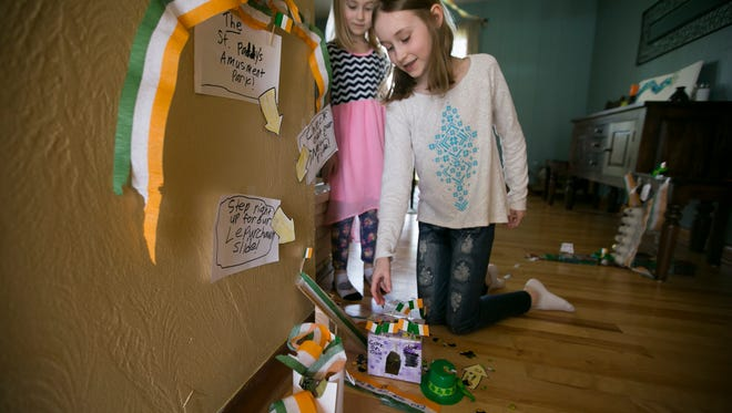Cora Sorem, 9, points on features of her leprechaun trap a few days before St. Patrick's Day as her sister Harper, 6, looks over her shoulder. Cora and her sisters have been setting traps for the mythical creatures for several years, and though they've never caught one, they say he often leaves behind small gifts for them to find. The family tradition has been going for several years, and Kate Sorem says it's a great way for her girls to have fun as they connect with their Irish heritage.