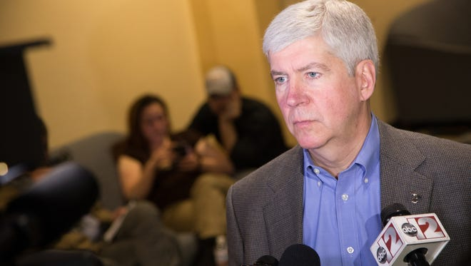 Governor Rick Snyder talks with press outside of the Flint Water Interagency Coordinating Committee meeting on Friday March 11, 2016, at the Riverfront Banquet Center in downtown Flint.