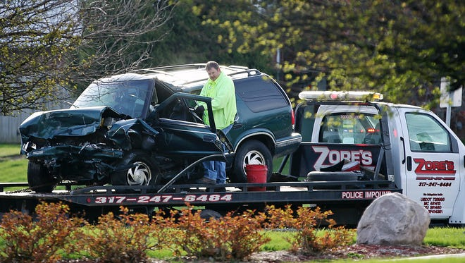 A vehicle is towed away from the scene of a fatal head-on collision, Wednesday morning, March 30, 3016, near South Madison Avenue and East Stop 11 Road, Southport, Ind. One person died and one has been hospitalized.