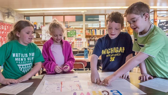 North Pennfield Elementary 2nd grade students, left to right, Haylee Pike, Alayna Houseman, Micah Lodes and Mason Keagle, go over their presentation for new businesses and attractions they would like to see in the Battle Creek area.