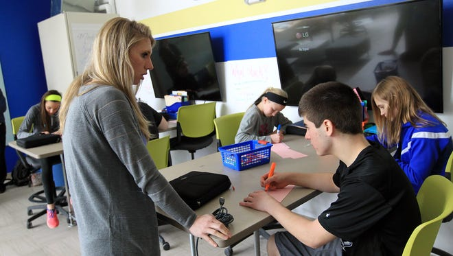 Teacher Reagan Boeset works with Clear Creek Amana seventh-grader Nate Beckmann during class inside the school's STEM Center in Tiffin on Wednesday, April 6, 2016.