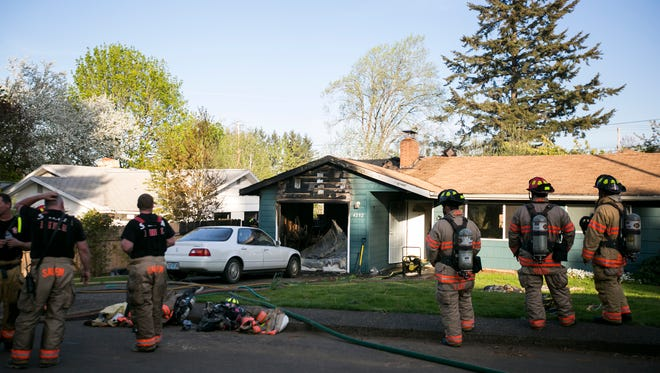 Firefighters clean up the scene of a garage fire in the 4200 block of McKay Drive S on Thursday, April 7, 2016.