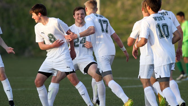 West High teammates congratulate Nicholas Raley (17) after his goal during the Trojans' game against Cedar Rapids Kennedy on Thursday, April 14, 2016.