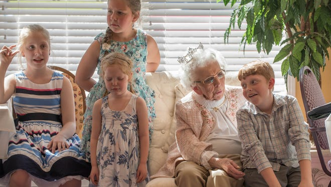 Young friends and relatives gather with  Mary Baird who is celebrating her 90th birthday. Baird share the same birthday date with Queen Elizabeth of England.