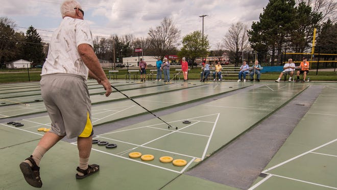 Larry Roan from Battle Creek during a game of shuffleboard at Bailey Park on Monday.