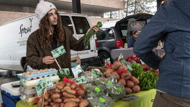 Manny Sevastopoulos of Sprout Urban Farms sells some chives during the first day of the Battle Creek Farm Market.