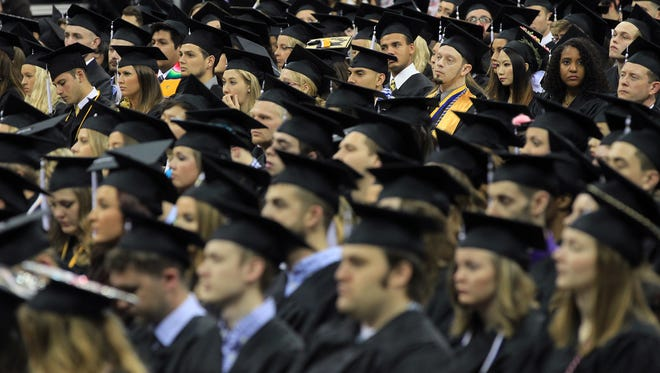 University of Iowa graduating students listen to senior Carter Bell during the UI commencement ceremony for the College of Liberal Arts and Sciences at Carver-Hawkeye Arena on Saturday, May 14, 2016.