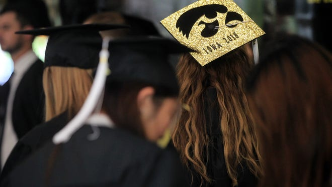 Taylor Tuthill of Dubuque dons a decorated cap during the University of Iowa commencement ceremony for the College of Liberal Arts and Sciences at Carver-Hawkeye Arena on Saturday, May 14, 2016.