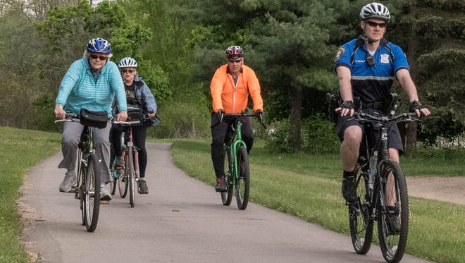 A small group led by Battle Creek police officer Craig Wolf go for a Slow Roll on the Linear Park path Monday evening. May is National Bicycle Month.