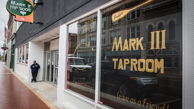Contractors and Mark III Taproom staff get the bar ready for opening night at their new location on Walnut Street Tuesday afternoon.