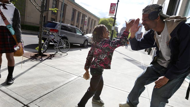 Lauren Newson, 6, of Detroit high fives her father, Michael Newson, as her sister Asia Newson, 13, left looks on, on Library Street downtown Detroit on Wednesday, May 18, 2016.Romain Blanquart/Detroit Free Press