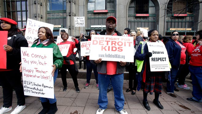 After declaring a school district wide sick-out for the second day, the Detroit Federation of Teachers take to the streets in front of the Fisher Building in Detroit Tuesday, May 3, 2016, to protest the threat to their pay.
