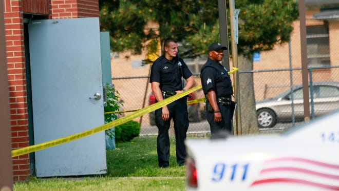 Police tape wraps around an  apartment complex where the body of a three-year-old boy was discovered on Wednesday by a maintenance worker, Detroit Police say.