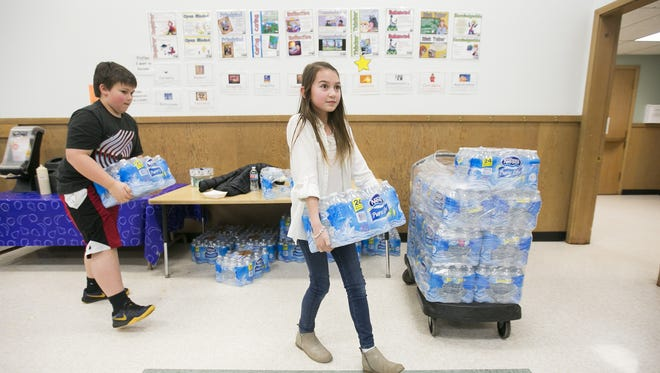 Fourth graders Emi Vu Magee and Brian Emmrich carry packages of bottled water back to their classroom at Valley Inquiry Charter School in Salem on Wednesday, March 16, 2016. Students and staff at the school have been drinking bottled water since March 2015, after high levels of copper were found in their water supply.