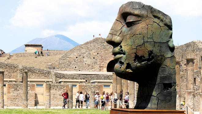 A sculpture by the late Polish artist Igor Mitoraj sits on the grounds of the Temple of Jupiter, with Mt. Vesuvius in the background.