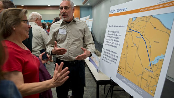 Joan Blankertz of Middletown talks with Larre Hozempa of JCP&L at the first of three open houses about its proposed project to construct a 10-mile transmission line along the NJ Transit tracks between Red Bank and Aberdeen.