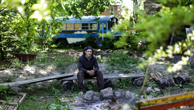 Karl Hughes, 32, lives at the anarchist collective called Trumbullplex in the Woodbridge neighborhood of Detroit and is photographed in one of the side lots located next to the collective's house on Wednesday, June 8, 2016.
