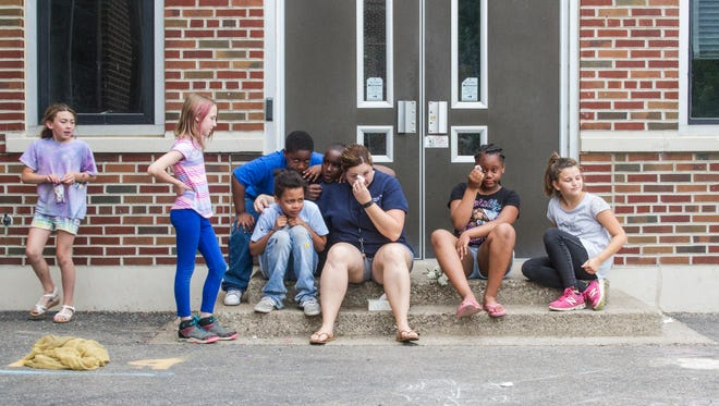 Fourth grade teacher Veronica Lopshire gathers with her students on the edge of the playground for a tearful goodbye at Urbandale Elementary School.