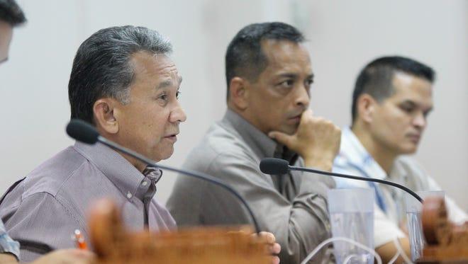 Sen. Tom Ada, left, poses a question during a wage increase public hearing at the Guam Legislature in April 2014.