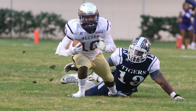 Alcorn State receiver Marquis Warford (10) tries to break away from Jackson State linebacker Kwame Bowens during last year's rivalry game in Jackson.