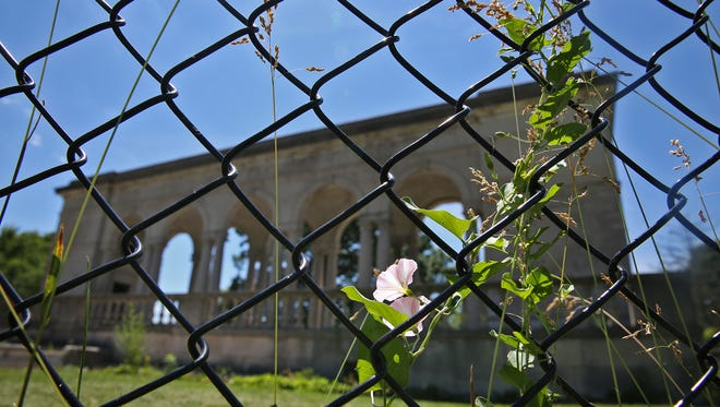 Weeds grow on a fence that surrounds the closed Thomas Taggart Memorial in Riverside Park on  Wednesday, June 8, 2016.  The limestone structure is crumbling and in need of repair.