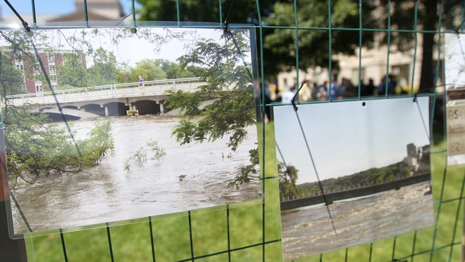 Photographs from the 2008 flood are pictured during an event celebrating the flood recovery at the Pentacrest on Wednesday, June 15, 2016.