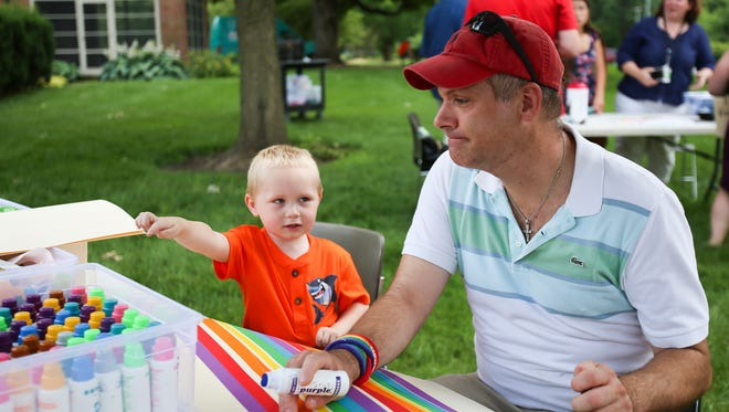 Rylan Abner, age 4 and Tim Franz make a poster to send their love to Orlando at the Indianapolis Museum of Art on June 19, 2016.